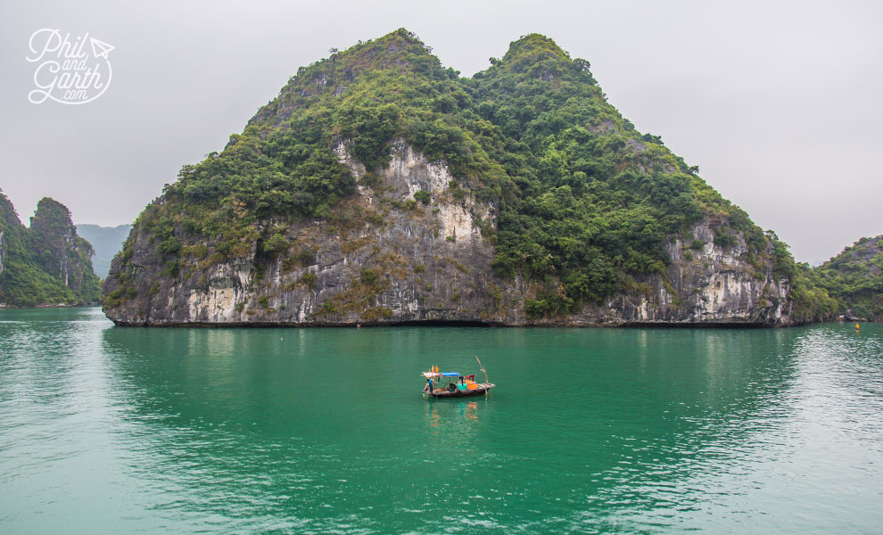A lone boat next to a towering karst island