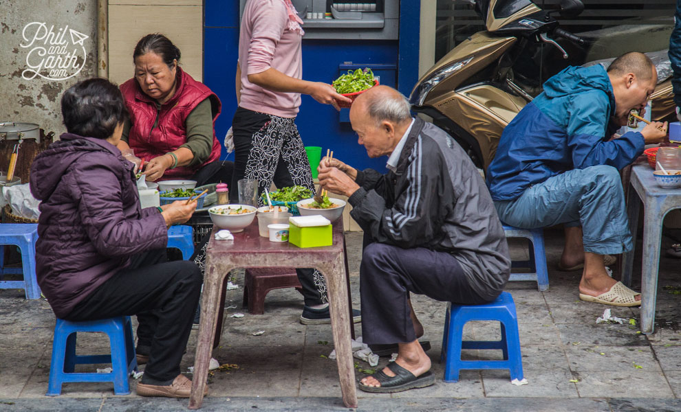 People enjoying street food in the Old Quarter