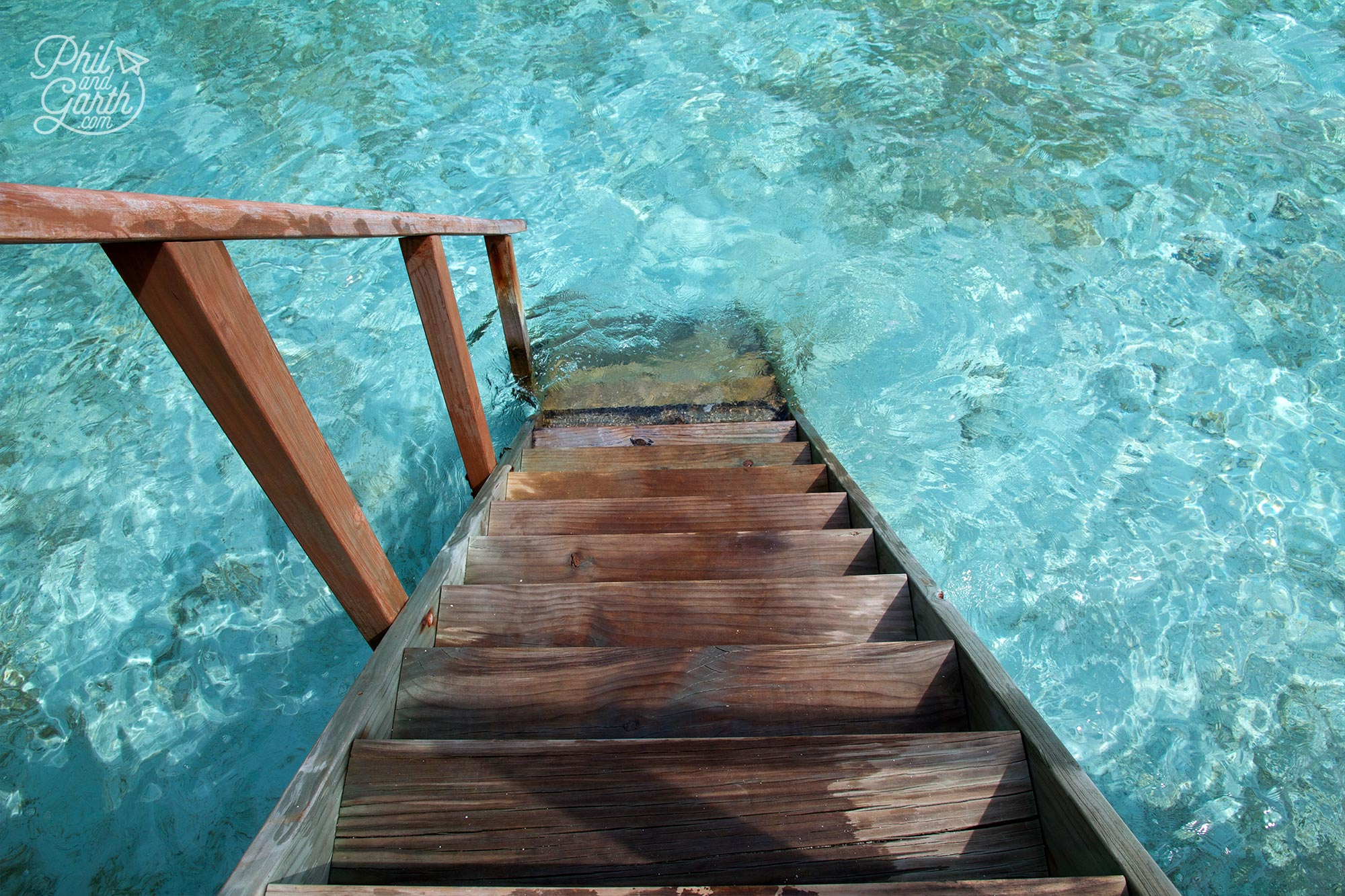 The steps down from our jacuzzi water villa straight to the water. Look at that colour!