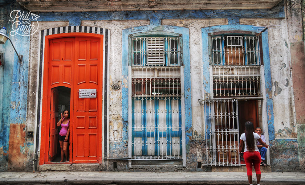 A lady stands in an impressive doorway in Old Havana
