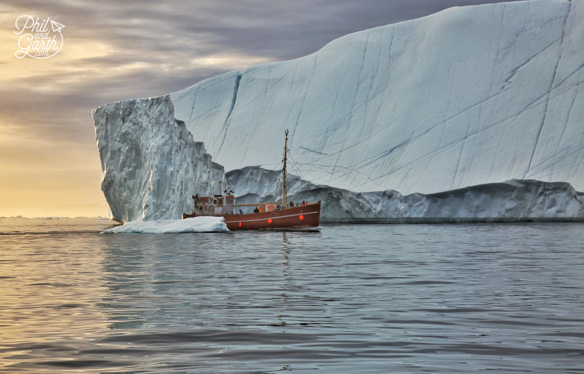 A fishing boat passes icebergs in the midnight sun