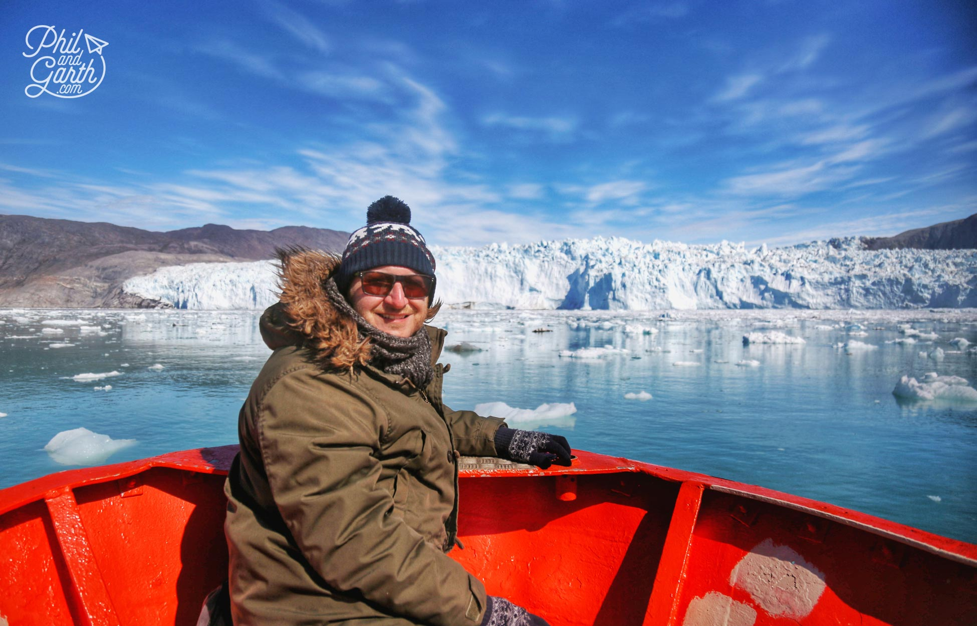 Garth approaching the Eqi Glacier by boat, with hat, gloves scarf and long johns!