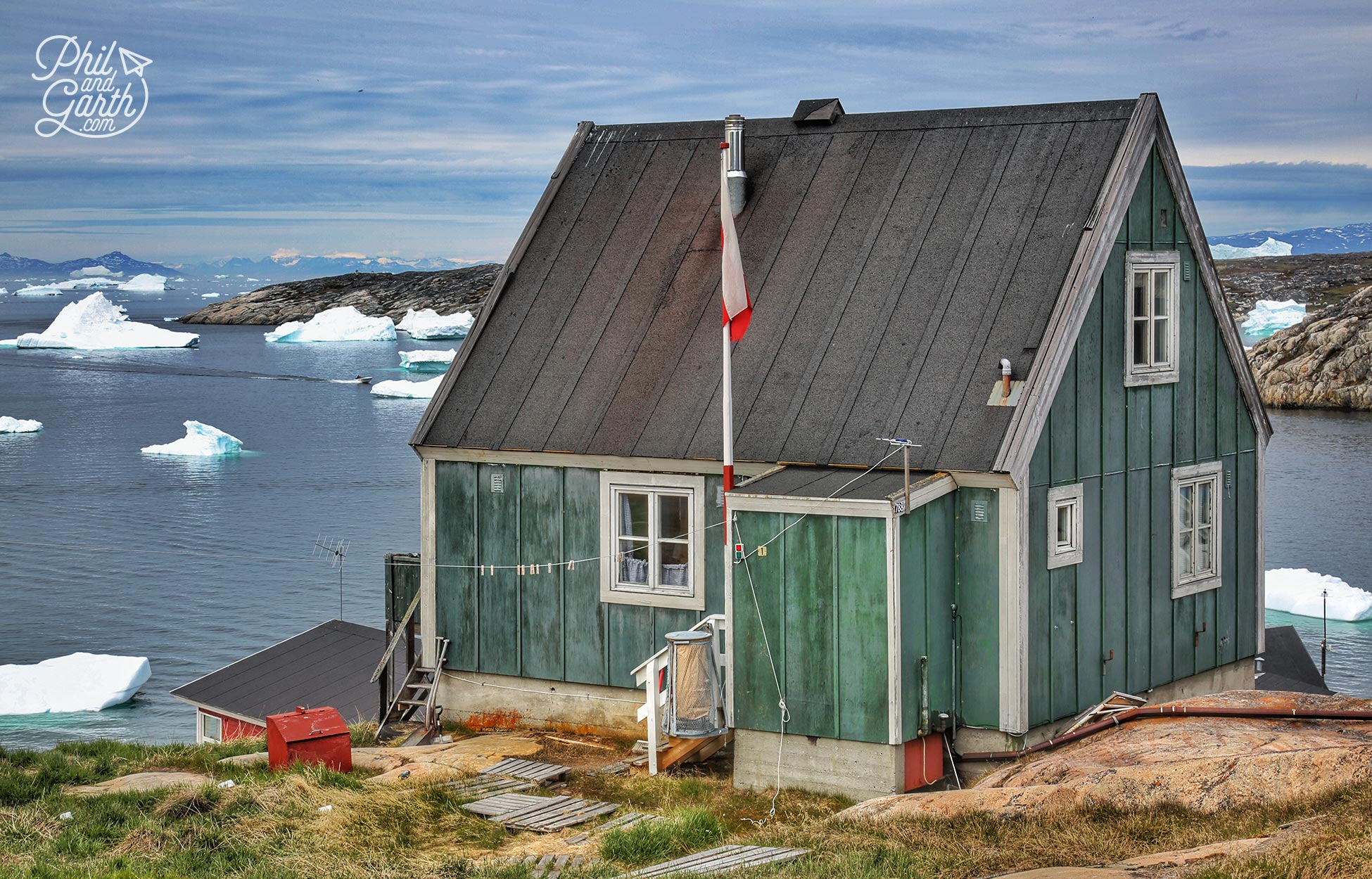 A lone house with the icebergs in Disko Bay, Ilulissat, Greenland