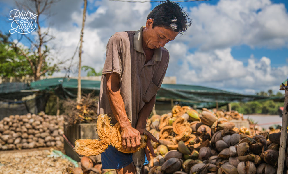 Worker removing the coconut husks