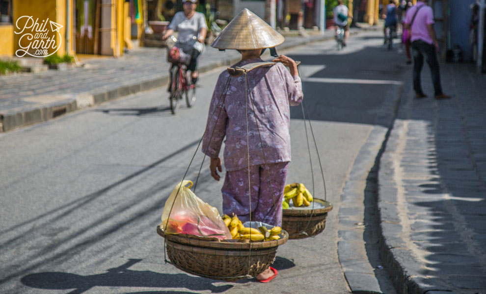 Fruit vendor carrying a traditional yoke with baskets full of bananas