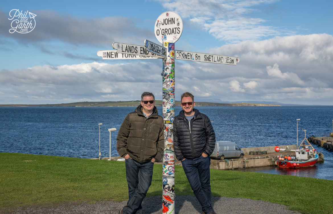 Phil and Garth at the John O' Groats landmark signpost, with the Orkney Islands in the background