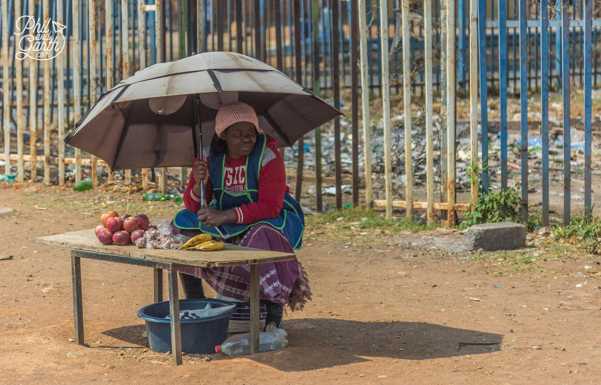 A lady sells a small amount of bananas, apples and nuts