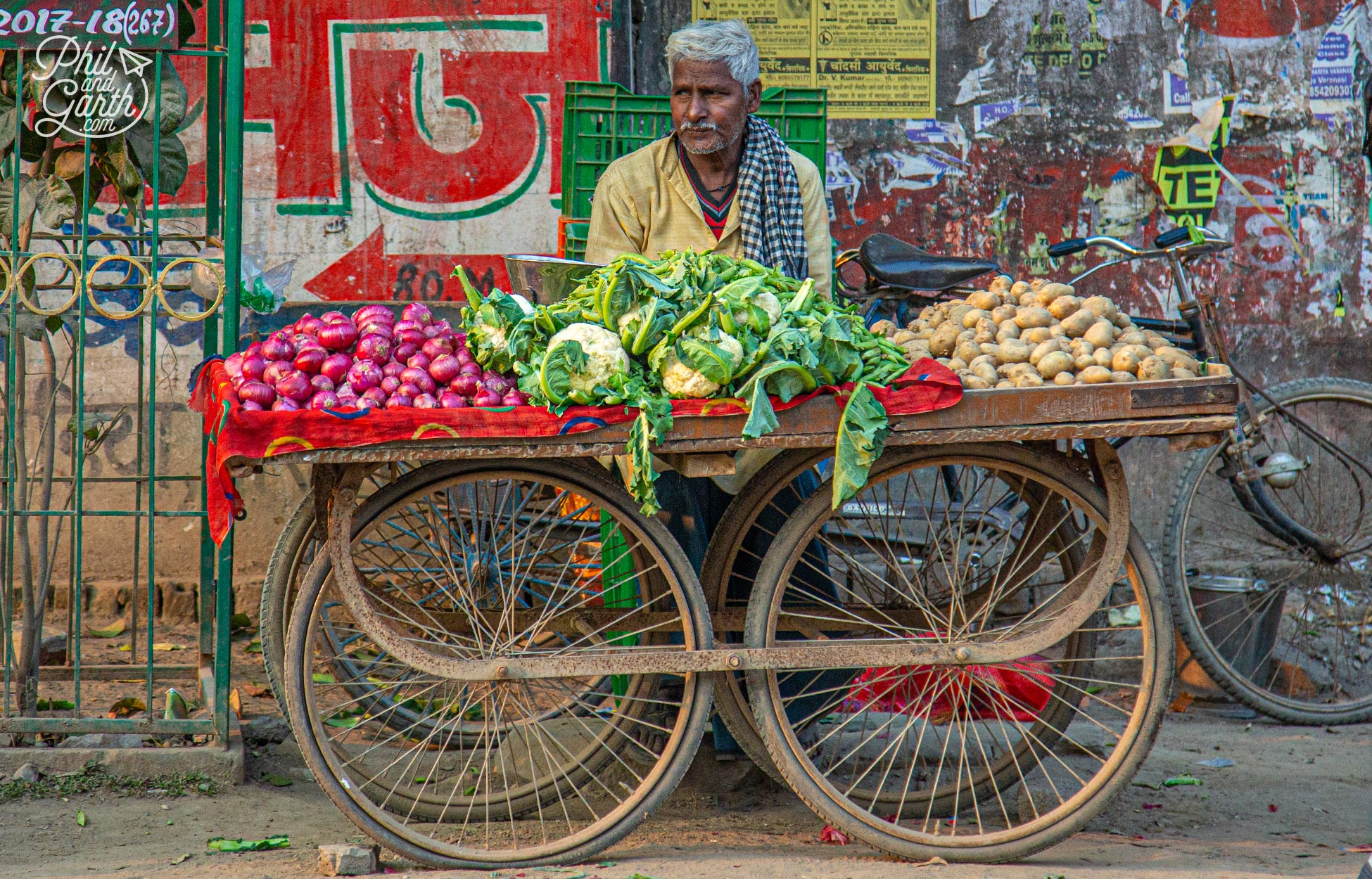 A guy selling onions, cauliflowers and potatoes