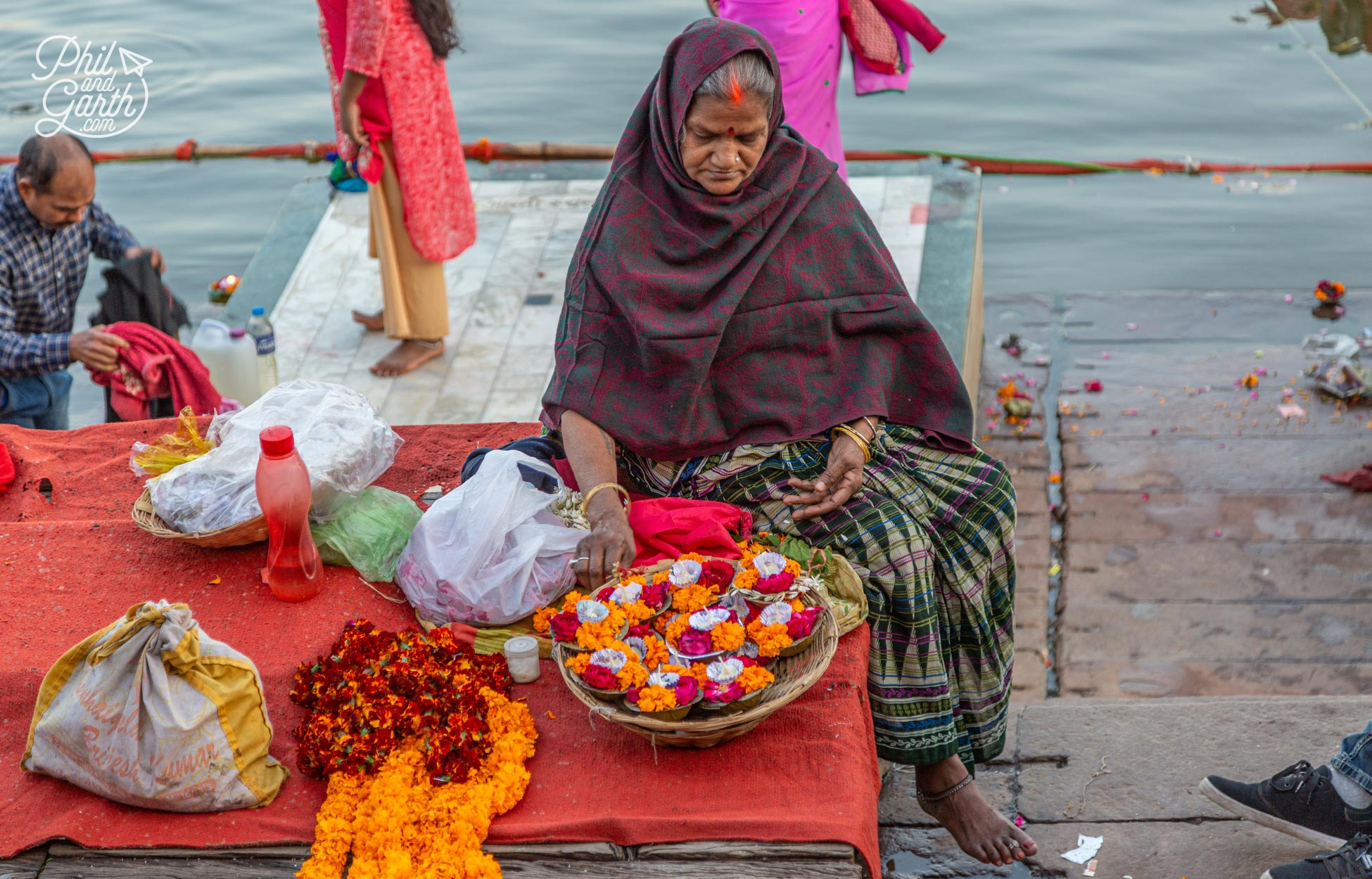 A lady makes candle and flowering offerings for the evening aarti