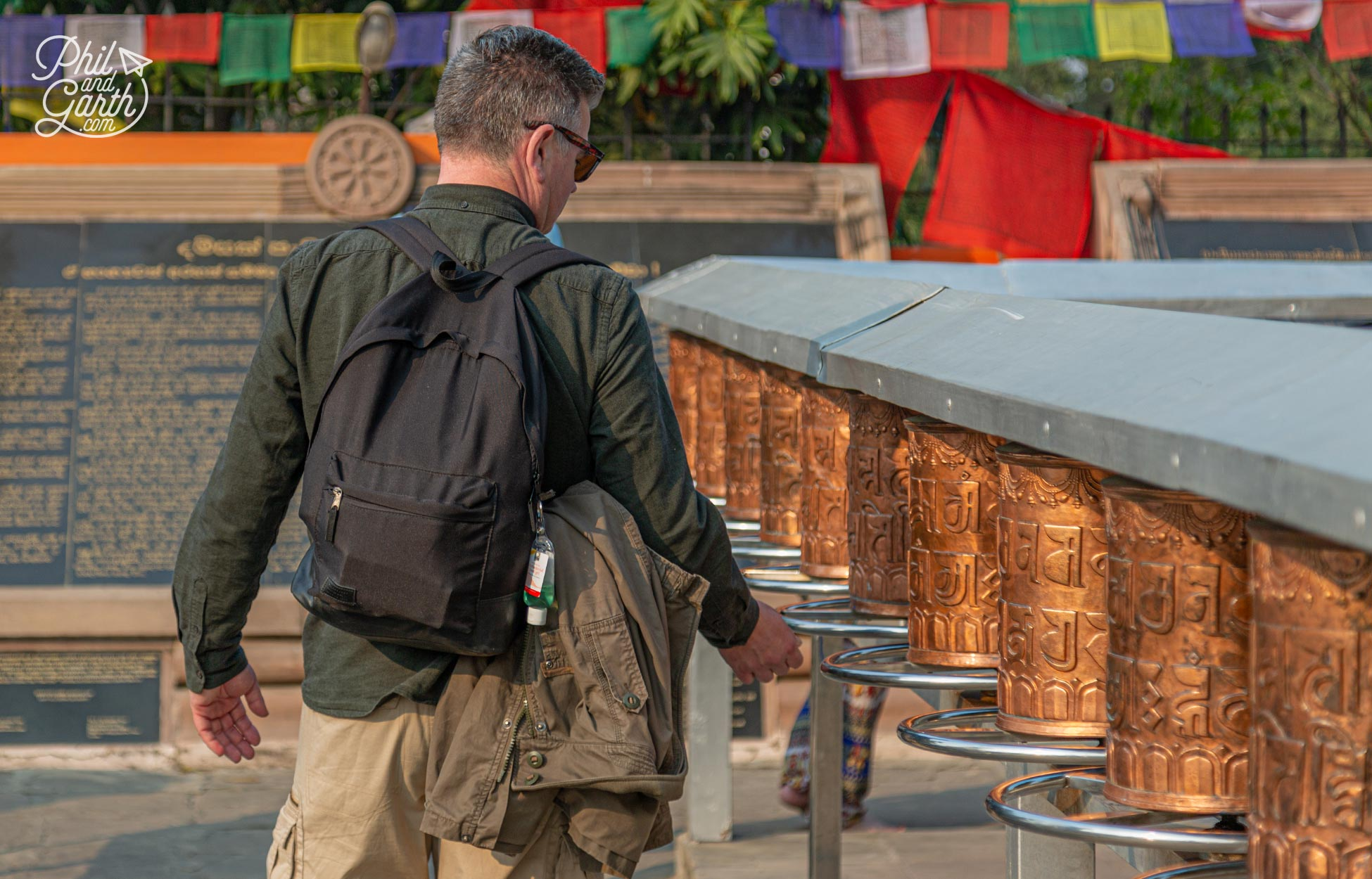 Phil spins the prayer wheels clockwise at the Mulagandha Kuti Vihara temple