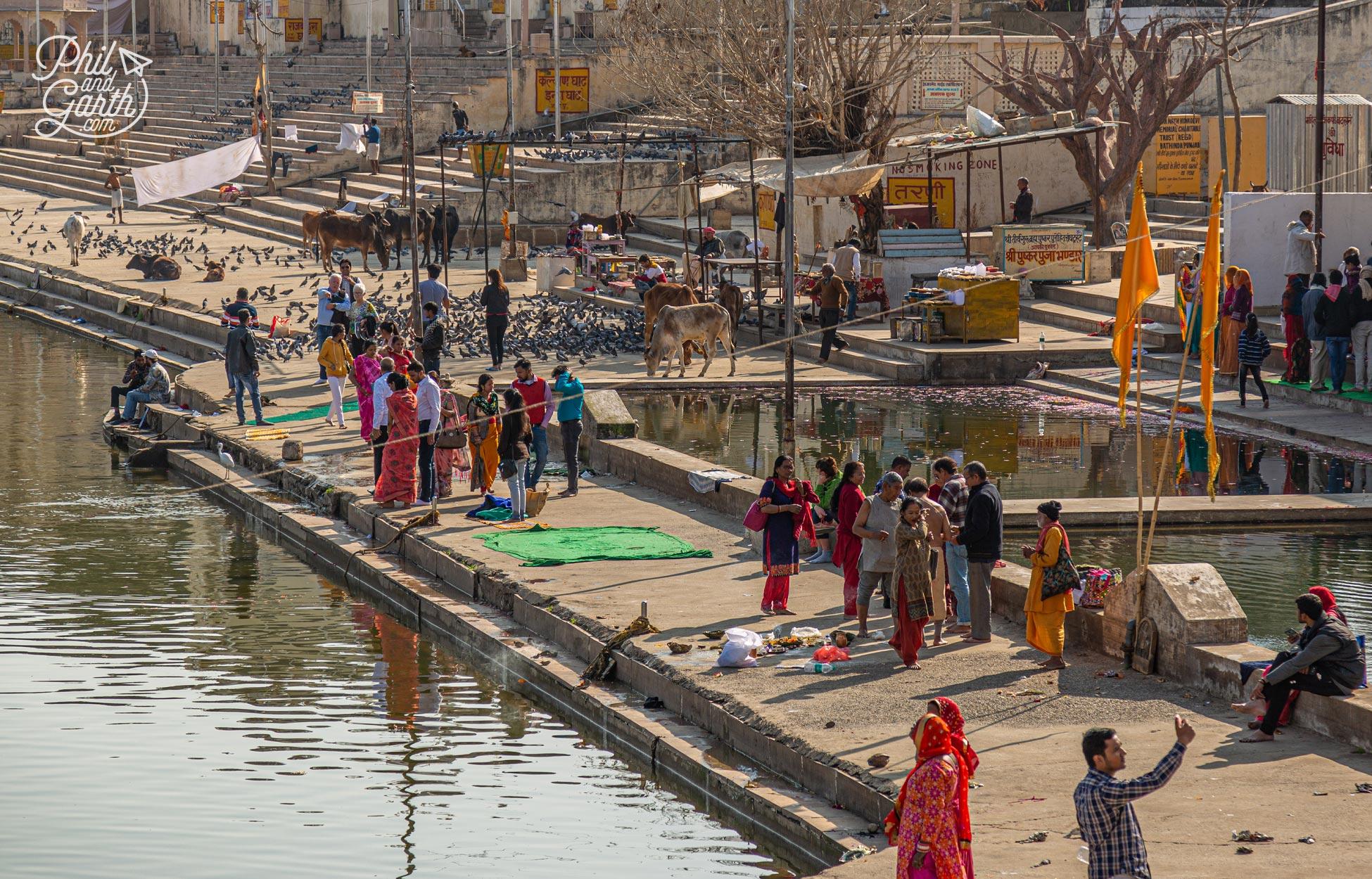 People leisurely strolling around Lake Pushkar taking selfies