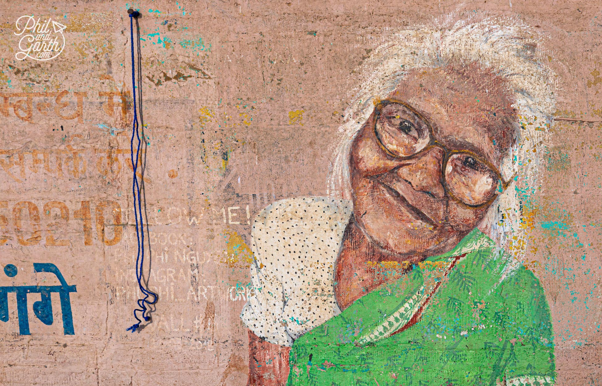 Street art in Varanasi - mural of an old lady on a pink wall