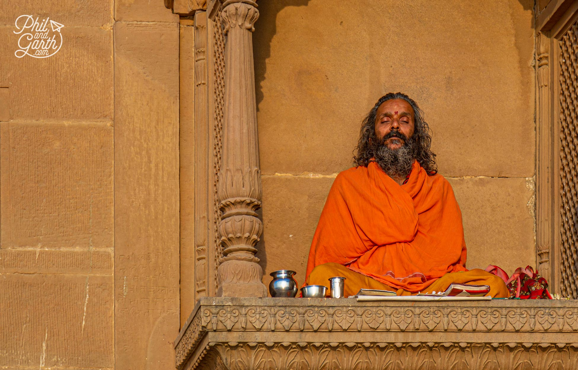 A sadhu meditating next to a temple