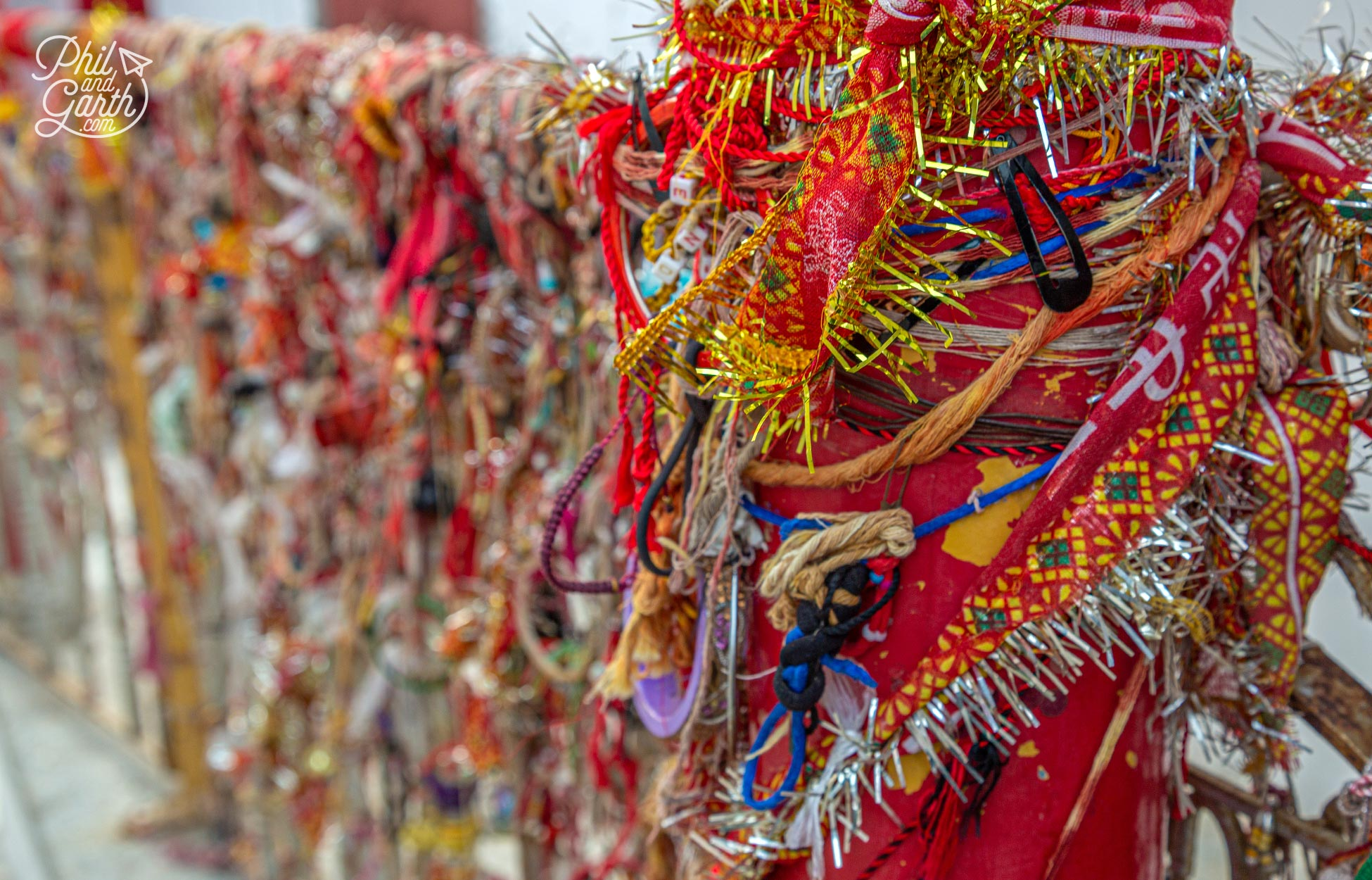 Hundreds of bracelets and strings of tinsel are tied to the temple's fence