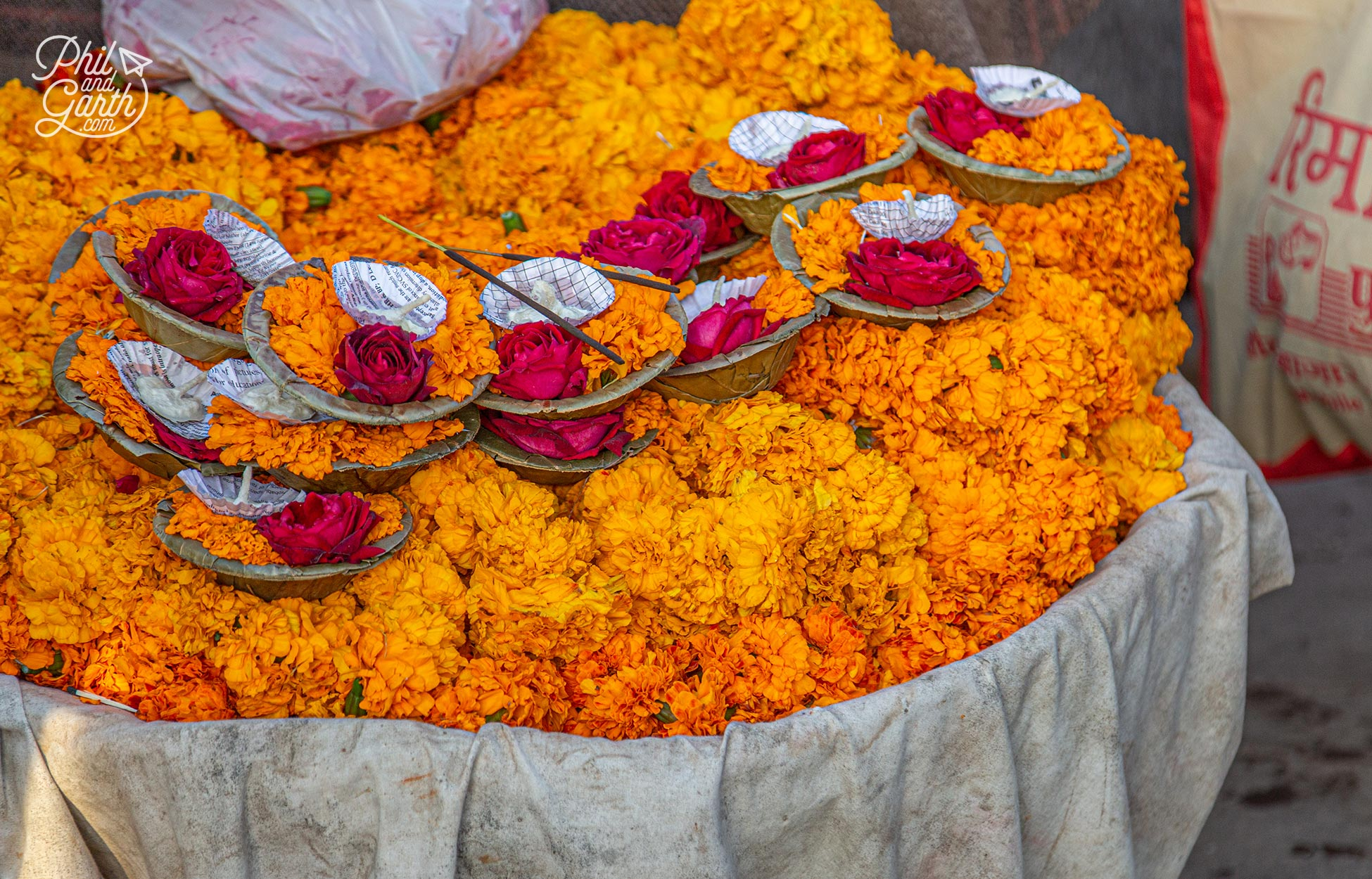 Deepaks for sale - little bowls containing a prayer candle, marigold and rose flowers