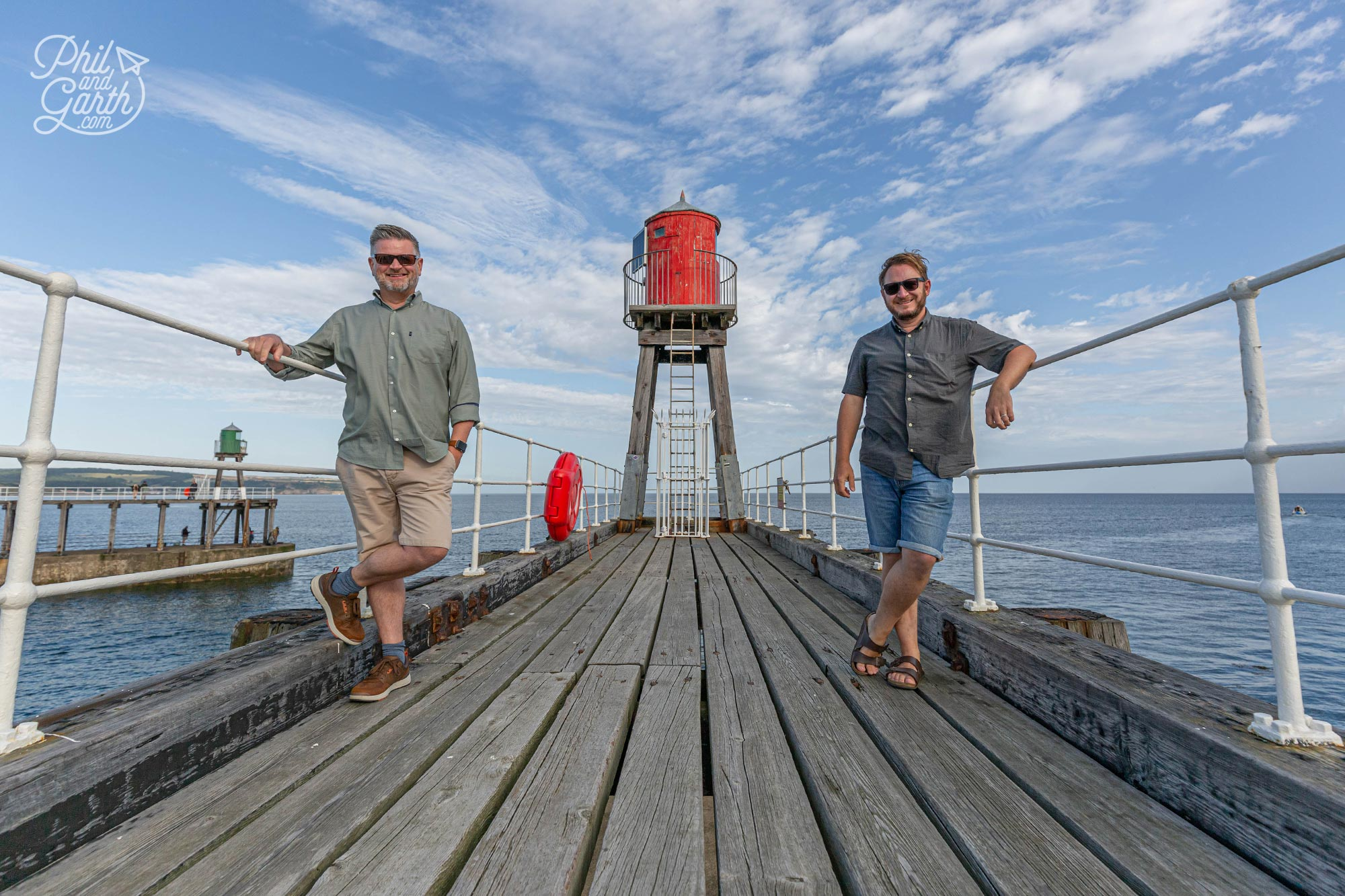 Phil and Garth standing on the wooden planks of the East Pier Whitby England