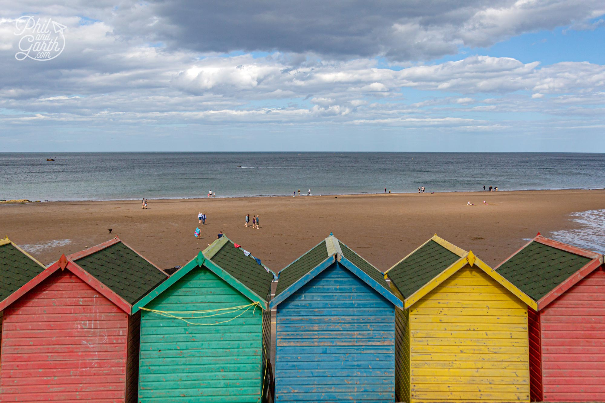 Rows of colourful beach huts along the promenade at Whitby Beach